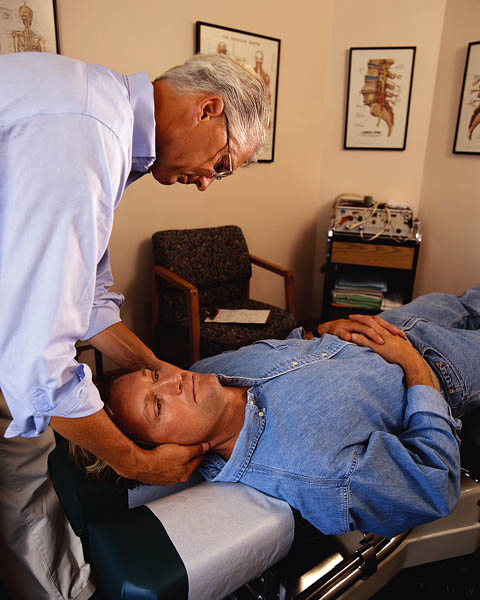 Chiropractor Adjusting Patient's Neck